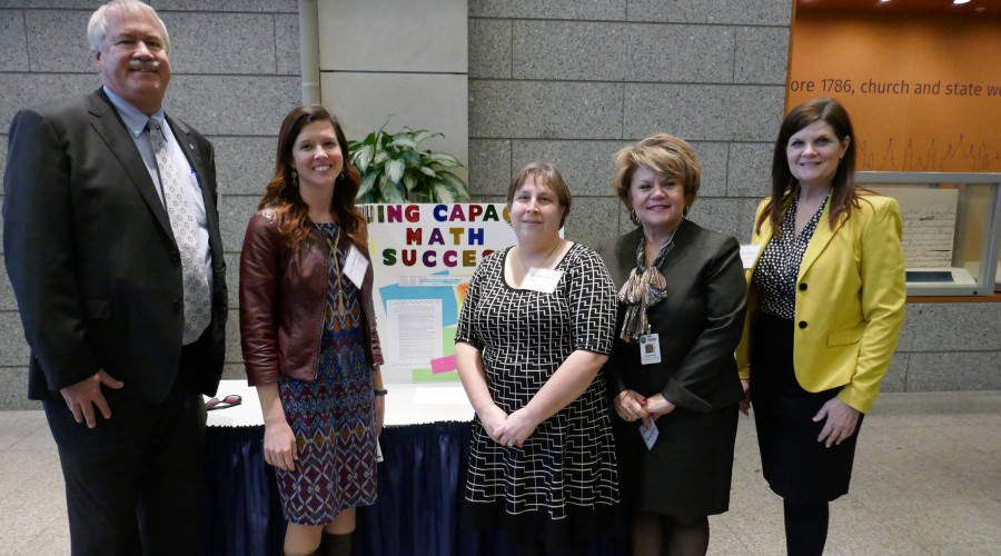 Five adults standing in front of a poster presentation.