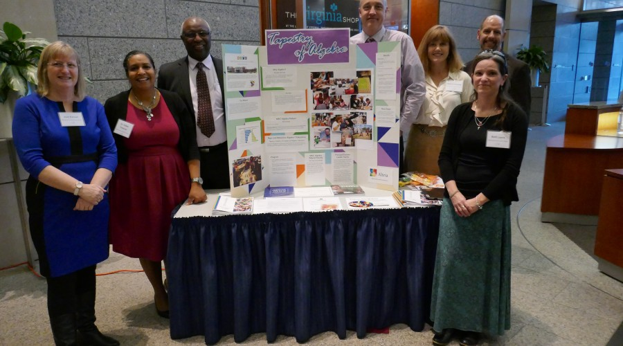 Six adults standing around a poster presentation.