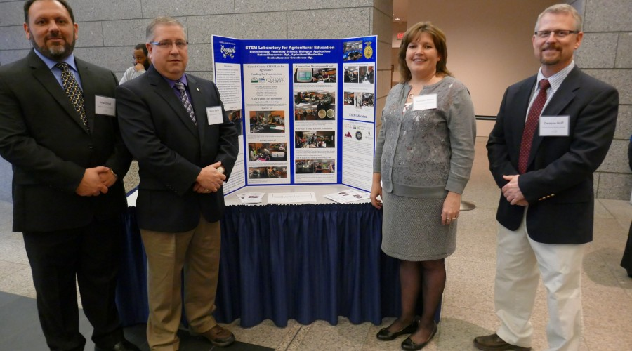 Two adults standing in front of a poster presentation.